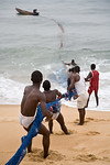 Sierra Leonean fishermen pulling in a large net from the sea