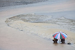 FREETOWN PENINSULA, SIERRA LEONE - AUGUST,2006: A young boy and girl with umbrella on the rainy beach. Beaches around the village of Sussex on the Freetown Peninsula. (Photo by: Christopher  ...