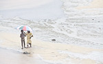 FREETOWN PENINSULA, SIERRA LEONE - AUGUST,2006: A young boy and girl with umbrella on the rainy beach. Beaches around the village of Sussex on the Freetown Peninsula. Sussex, Freetown Penins ...