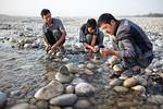 Young men looking for jade in river near Hotan, Xinjiang, China.