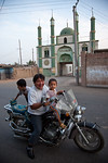 Father with his sons on a motorbike in front of a small mosque in Turpan, Xinjiang, China.