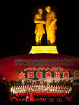 Culture performance under a statue of Mao and a senior Uyghur man in Hotan, Xinjiang, China.