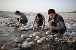 Hotan, Xinjiang, China - September 29, 2009: Young men at sunrise sorting through rocks in the Yorungqash or White Jade River in hopes of finding some Jade.  (Photo by: Christopher Herwig)