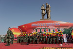 Hotan, Xinjiang, China - September 29, 2009: Chinese soldier in front of a communist propaganda statue of Chairman Mao shaking hands with a shorter Uyhgur man. After riots in Urumqi in July  ...