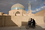 Yazd, Iran - February, 2008:Couple on a motorbike ride past the eleborately tiled 14th century Jameh (Friday) Mosque with 48 meter high minarets in the old town in Yazd, Iran. (Photo by Chri ...
