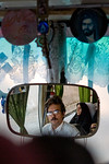 Dasht e Kavir, Iran - February, 2008: Bus driver and female passenger dressed in black reflected in the mirror of a bus enroute through the desert from Esfahan to Khur in Central Iran. (Phot ...
