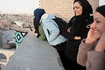 Yazd, Iran - February, 2008: Group of young Iranian girls enjoying a rooftop view over the desert city of Yazd, famous for its many wind towers which act as a natural air conditioner. (Photo ...
