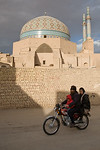 Yazd, Iran - February, 2008: Family on a motorbike ride passed the eleborately tiled 14th century Jameh (Friday) Mosque with 48 meter high minarets in the old town in Yazd, Iran. (Photo by C ...